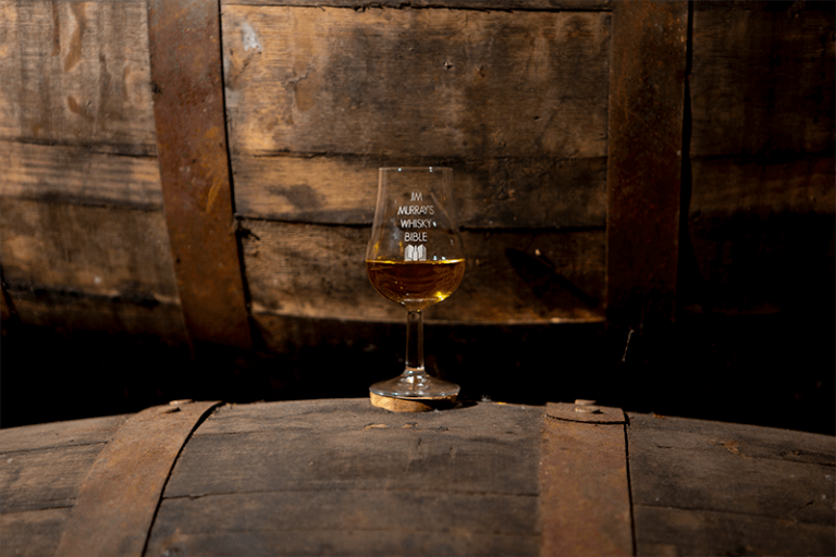 A single glass on a barrel
